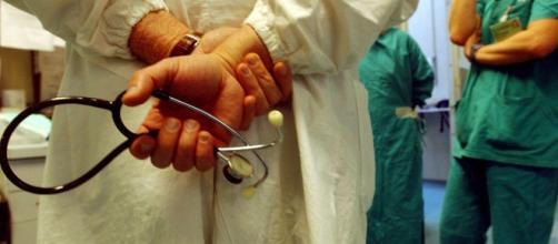 Medico con stetoscopio in consulta con alcuni colleghi
