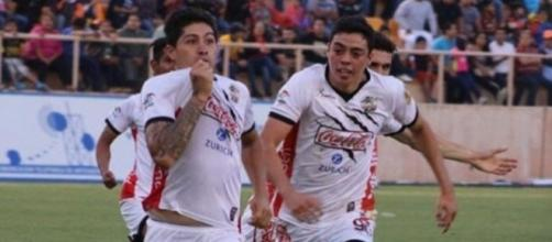 Amaury Escoto (izq.) besa su playera tras anotar el 1-2 parcial. (vía twitter - BigBoiler).