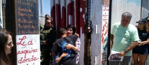 Menor de edad abrazando a su hermana y madre quienes viven del otro lado de la frontera