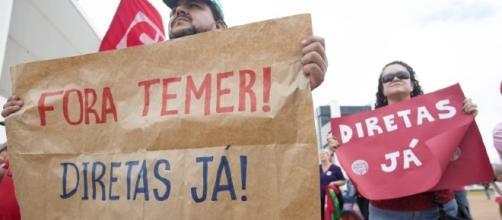 Manifestantes seguram cartazes durante a manifestação no domingo (21) (Foto: Reprodução)