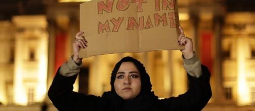 A Muslim woman holds a sign ... - go.com