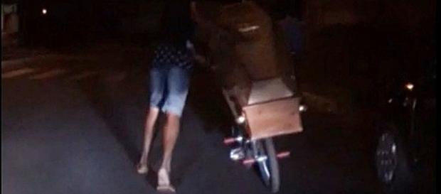 Homem foi gravado por populares andando com caixão na bicicleta