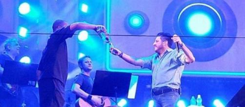 Foto mostra Bruno bebendo no palco durante show e Patos de Minas (Fonte; Reprodução/Vídeo)