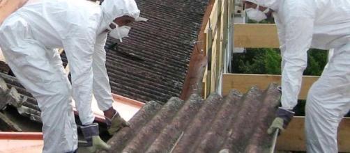 Due uomini al lavoro mentre rimuovono materiale dove è presente amianto