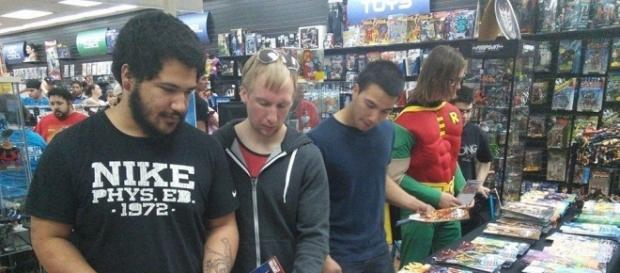 Customers pick up copies of free comics made available at a comic shop. [Image via Blasting News image library/levelupentertainment.com]