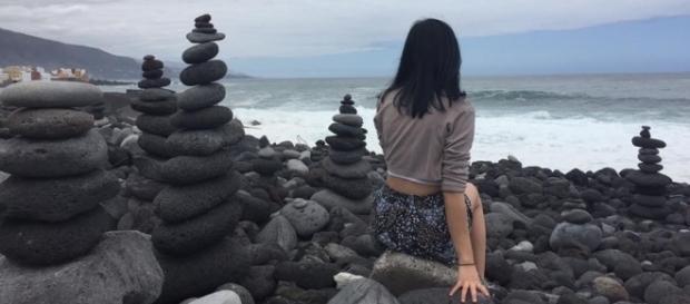 Chica italiana alrededor de apachetas en la playa del Castillo San Felipe, Puerto de la Cruz