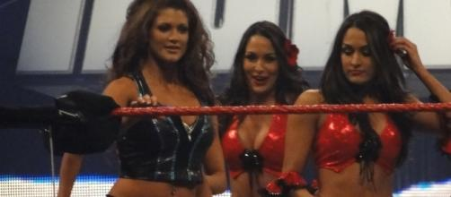 Former WWE Divas champions Eve Torres and The Bella Twins appear in ring together. [Image via Wikimedia Commons]