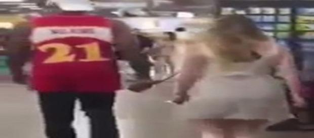O rapaz segura uma coleira que está presa no corpo da mulher. (Foto/Youtube)