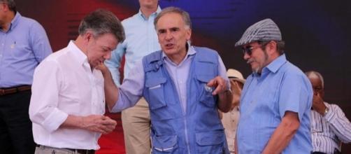"""Juan Manuel Santos, izquierda, Jean Arnault, jefe de la """"Misión de la ONU"""", centro , Timochenko, derecha."""