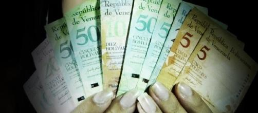 En la imagen, una mujer con billetes en la mano desplegados