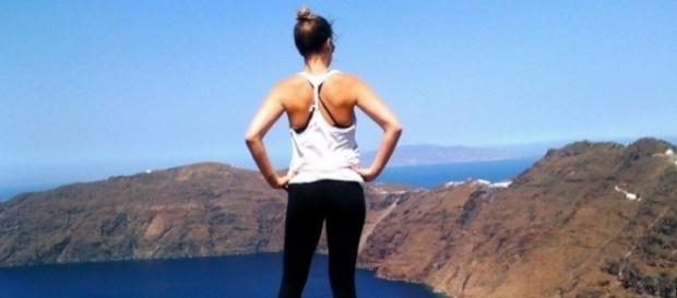 Turista contemplando o horizonte na ilha de Santorini, Grécia