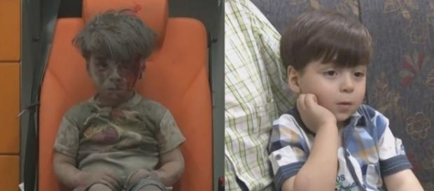 Menino de Aleppo resgatado com o rosto sujo de sangue, revê a própria imagem em um celular.