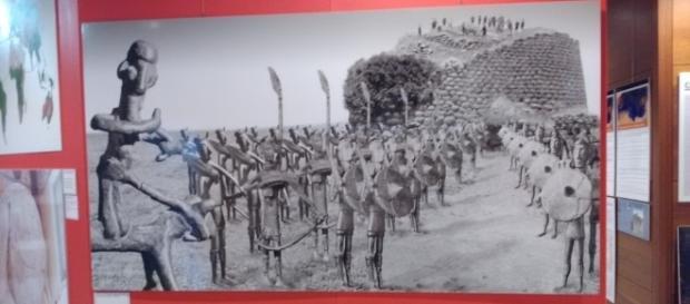 Foto della mostra Omphalos raffigurante un nuraghe e un esercito di bronzetti nuragici.