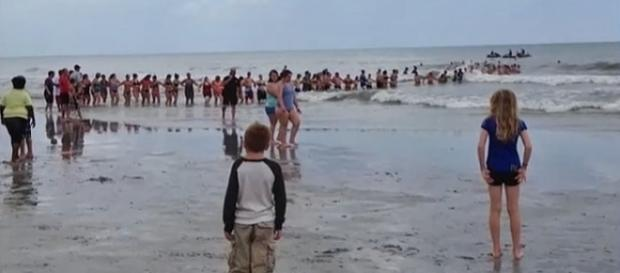 Photo human chain rescues family caught in riptide screen capture via YouTube/The Last News