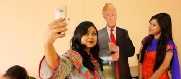 Clientes fazem selfie com efígie do presidente norte-americano Donald Trump, no Trump Cafe, em Bangladesh (Foto: Reprodução/Abir Abdullah/EFE)