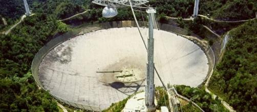 The Arecibo Radio Telescope, at Arecibo, Puerto Rico by H. Schweiker/WIYN and NOAO/AURA/NSF via Wikimedia Commons