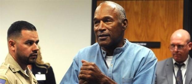 O.J. Simpson clasps his hands in joy after being granted parole from Las Vegas robbery case. (Image Credit: nbcnews.com)