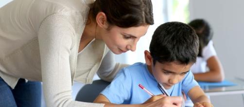 Bambino che fa i compiti a scuola con la maestra