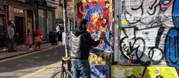 """Muñiz colocando un collage en Brick Lane, Londres, llamado """"There's no place like London"""". 30 de julio de 2017."""