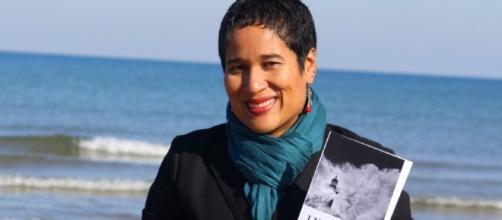 la scrittrice e attivista politica Ilka Corado mostra sorridendo uno dei suoi libri