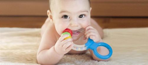 A baby with teether (Image Source: YouTube/Babies Wiki)