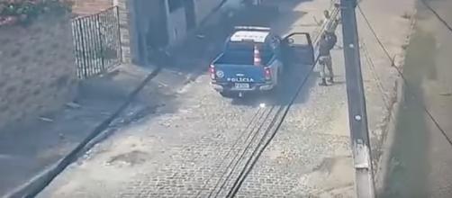 Homem avança, com facão visível em sua mão direita, contra policial