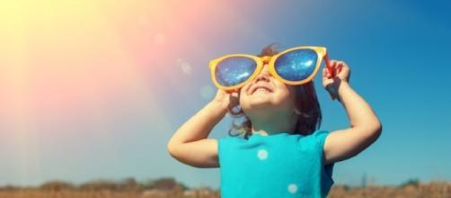 Bambina con occhiali sotto il sole accecante