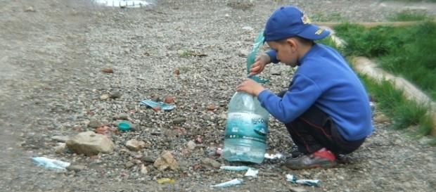 Niño pobre con sus juguetes: una botella vieja de agua y piedras.