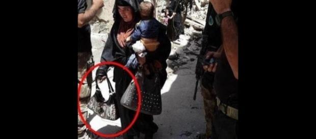 Mulher-bomba carregando seu bebê em um dos braços foi fotografada no Iraque momentos antes de detonar explosivos que transportava em uma bolsa