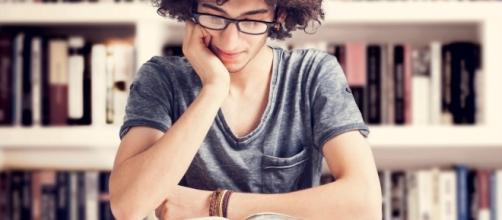 Jovem estudando em biblioteca para ser estagiário ou trainee