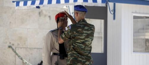 Soldado grego seca o rosto de um 'Evzone' durante o intenso calor na Grécia neste ano