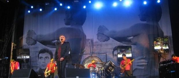 Morrissey on stage with band - photo by Alexander via Wikimedia Commons.