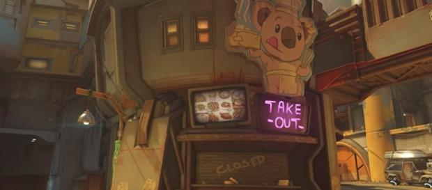 """The signage in a Junkertown restaurant reads """"take out,"""" which is a common American expression. (Gamespot/Blizzard)"""