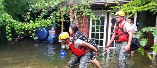 A National Guardsman carries an evacuee to safety. [Image via US Department of Defense]