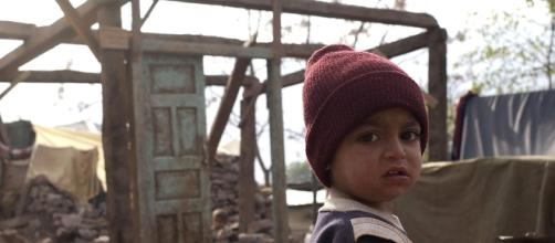 A child is shown amidst rubble of a destroyed home (Barry Loo/Wikimedia Commons).