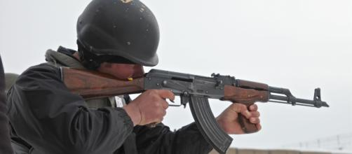 An Afghan uniformed police officer fires his AK-47 rifle.Source;commons.wikimedia.org