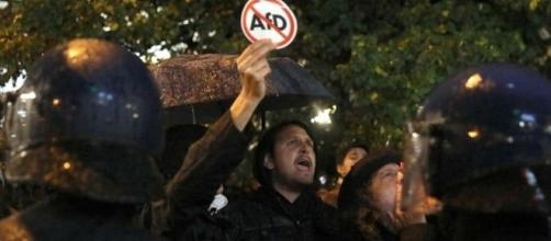 Manifestante antifascista davanti al cordone di polizia con un cartello anti-AfD