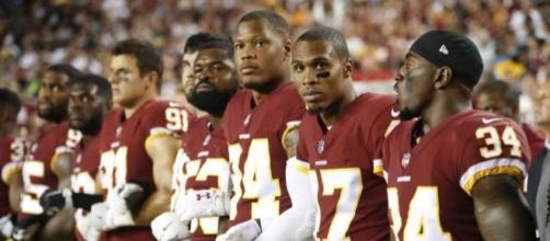 (Washington Redskins link arms in protest, courtesy BipHoo Company/Flickr)