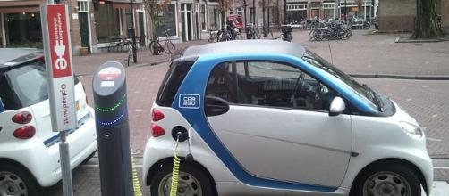 Electric car at charging station (image courtesy of Ludovic Hirlimann wikimedia commons)