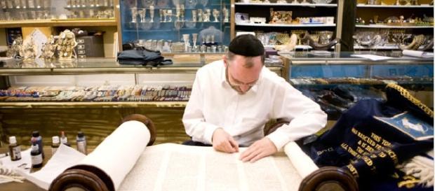 Rabino interpreta a Torá, escrita no pergaminho