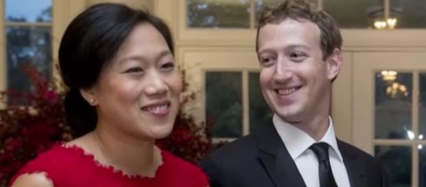 Mark Zuckerberg cuddles newborn daughter, August. YouTube/Bloomberg