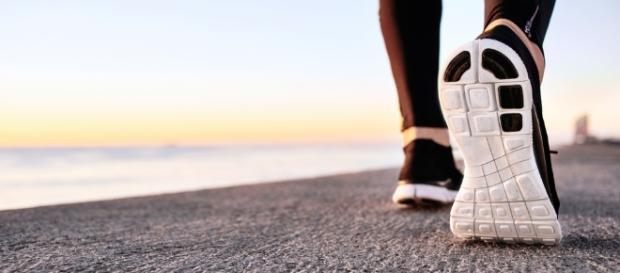 Pessoa caminha na praia (Esporte e lazer)