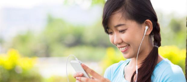 Una chica sonríe mientras escucha música.