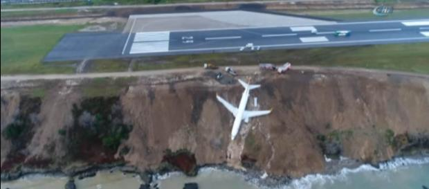 A Turkish passenger jet had problems landing and skidded off the runway, hanging from a cliff [Image credit: Ihlas News Agency/YouTube]