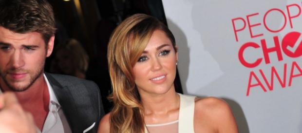 Miley Cyrus and Liam Hemsworth on the red carpet at the 38th People's Choice Awards (Image via Jessica /Commons.Wikimedia.org)