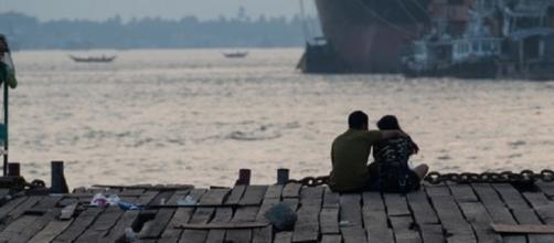 Esta foto fue tomada el 26 de abril de 2017 y muestra una pareja sentada en un embarcadero durante el atardecer en Yangon.