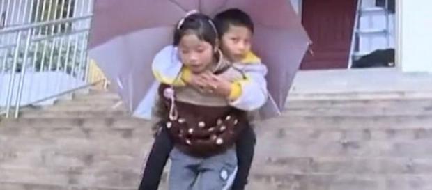 O fetiță în vârstă de 9 ani din China, își duce în fiecare zi în spate la școală fratele - Foto: Daily Mail (© Wenshan Television Station)