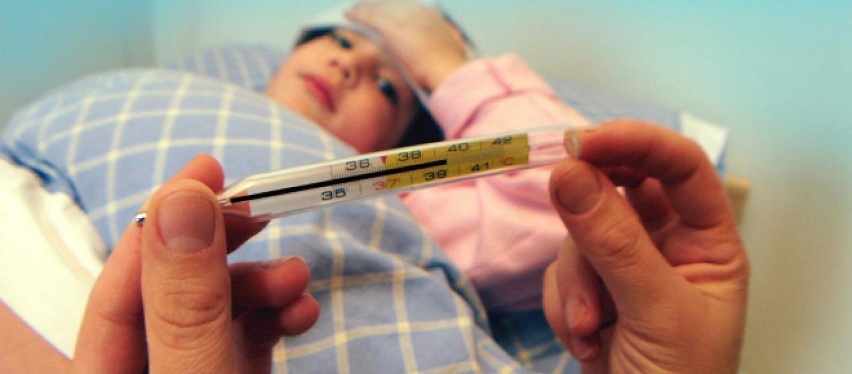 Nella foto la vista un particolare di una mano che tiene un termometro vecchio stile al mercurio la temperatura misurata è alta
