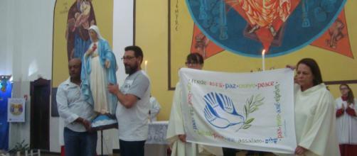 Paroquianos com imagem da Mãe de Jesus e bandeira simbolizando a paz