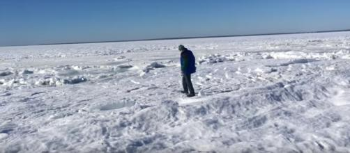 A man walks on the frozen ocean off Old Silver Beach - North Falmouth, MA. [image source: Ryan Canty / Youtube screenshot ]